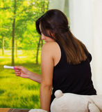 Pretty young brunette woman sittin down while looking at pregnancy home test, back facing camera, bookshelves and garden Royalty Free Stock Photos