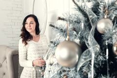 Pretty young brunette woman standing near fir tree in Christmas Royalty Free Stock Photos