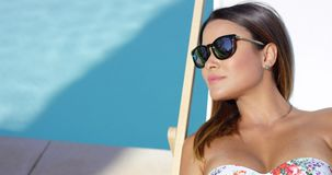 Pretty young brunette woman sunbathing poolside stock footage