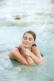Pretty young brunette woman taking a bath in the natural thermal waters of spa Stock Image