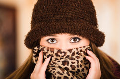 Pretty young brunette woman wearing brown hat and scarf covering up face revealing only eyes, staring straight into Royalty Free Stock Photos
