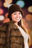 Pretty young brunette woman wearing fur style jacket, hat and scarf posing happily with a glamorous blurry light drops Stock Image