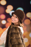 Pretty young brunette woman wearing fur style jacket, hat and scarf posing happily with a glamorous blurry light drops Royalty Free Stock Photography
