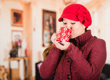 Pretty young brunette woman wearing red sweater and beenie, taking a sip from cup of hot beverage Stock Images