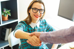 Pretty young business woman with arm extended to handshake Royalty Free Stock Photo