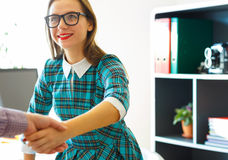 Pretty young business woman with arm extended to handshake. Modern young business women with arm extended to handshake Stock Photography