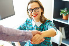 Pretty young business woman with arm extended to handshake. Modern young business women with arm extended to handshake Royalty Free Stock Photo