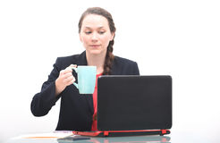 Pretty young business woman drinking coffee at work Stock Photography