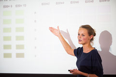 Pretty, young business woman giving a presentation. In a conference/meeting setting (shallow DOF; color toned image stock photos