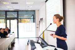 Pretty, young business woman giving a presentation. In a conference/meeting setting (shallow DOF; color toned image stock photography
