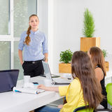 Pretty young business woman giving a presentation in conference or meeting setting. People and teamwork concept - happy Stock Images
