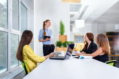 Pretty young business woman giving a presentation in conference or meeting setting. People and teamwork concept - happy Royalty Free Stock Images