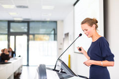 Pretty, young business woman giving a presentation Stock Images