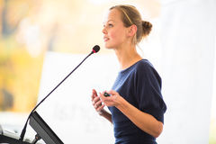 Pretty, young business woman giving a presentation. In a conference/meeting setting (shallow DOF; color toned image royalty free stock photos