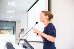 Pretty, young business woman giving a presentation. In a conference/meeting setting (shallow DOF; color toned image royalty free stock images