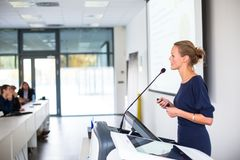 Pretty, young business woman giving a presentation in a conference. /meeting setting shallow DOF; color toned image royalty free stock photos