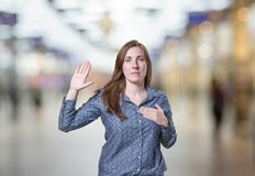 Pretty young business woman making an oath over blur background stock image