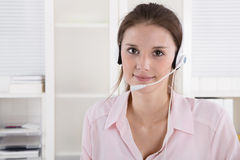 Pretty young business woman in rose blouse with headset. Royalty Free Stock Photography