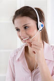Pretty young business woman in rose blouse with headset. Stock Images