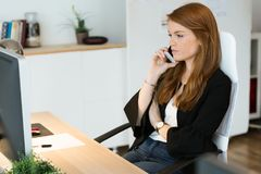 Pretty young business woman using her mobile phone in the office. royalty free stock image