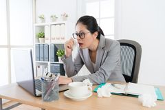 Pretty young business woman using mobile laptop. Pretty young business women using mobile laptop working in office and feeling uncomfortable when she catches Stock Photos