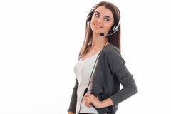 Pretty young business woman working in call center with headphones and microphone looking away and smiling isolated on Royalty Free Stock Photography