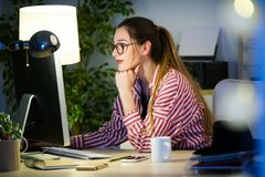 Pretty young business woman working with her laptop in the office. Royalty Free Stock Images