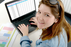 Pretty young business woman working at laptop in office Stock Photography
