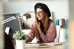 Pretty young business woman working with laptop while using her mobile phone in the office. Royalty Free Stock Photography