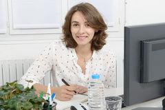 Pretty young business woman working at pc in office Stock Images