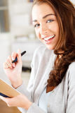Pretty young business woman writing Stock Photo