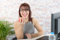 Pretty young businesswoman eats an apple Royalty Free Stock Images