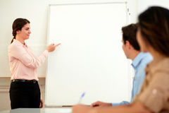 Pretty young businesswoman pointing at whiteboard Royalty Free Stock Photos