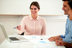 Pretty young businesswoman smiling and pointing Stock Photo