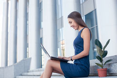 Pretty young businesswoman is using a laptop for Stock Image