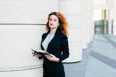 Pretty young businesswoman wearing black jacket, skirt and white blouse, holding her pocket book with pen, writing notes or lookin stock photos