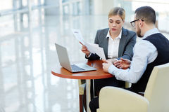 Pretty Young Businesswoman Working with Client in Meeting. Portrait of young businesswoman consulting client on contract terms finalizing the deal Royalty Free Stock Photography