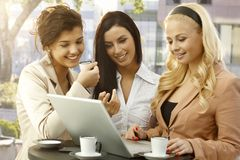 Pretty businesswomen using laptop outdoors. Pretty young businesswomen standing in outdoor cafe, using laptop computer, smiling happy Stock Photos
