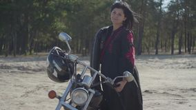 Pretty young caucasian brunette girl standing at the motorcycle looking away in front of pine forest. Hobby, traveling. The girl with black hair standing at the stock footage