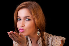 Pretty young caucasian girl sending kiss. With golden reflexion, isolated on black, studio shot Stock Photos