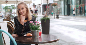 Pretty young caucasian girl sitting at cafe and smiling to a camera. Stock Photo