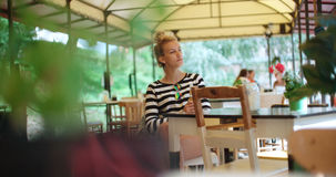 Pretty young caucasian girl sitting at outdoors cafe and waiting for someone. Young attractive woman sitting alone in cafe Stock Images