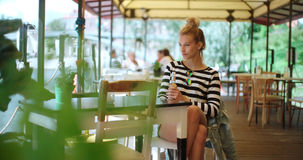 Pretty young caucasian girl sitting at outdoors cafe and waiting for someone. Young attractive woman sitting alone in cafe Stock Image