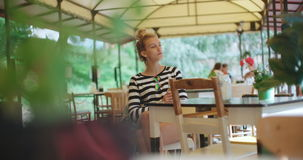Pretty young caucasian girl sitting at outdoors cafe and waiting for someone. stock footage