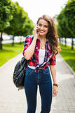 Pretty young caucasian woman with backpack speaking on the phone Royalty Free Stock Photo