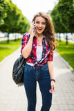 Pretty young caucasian woman with backpack speaking on the phone Stock Images