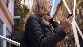 Pretty young Caucasian woman in the jacket and sunglasses walking with a smartphone in her hands and wearing headphones stock video
