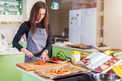 Pretty young Caucasian woman making pizza by recipe book, chopping vegetables on cutting board in her flat. Pretty young Caucasian woman making pizza by recipe Stock Photo