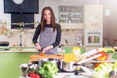 Pretty young Caucasian woman making pizza by recipe book, chopping vegetables on cutting board in her flat. royalty free stock photography