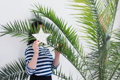 Pretty young caucasian woman in stripped vest hiding behind white LED glowing star and green palm leaves. Summer fashion concept stock photos